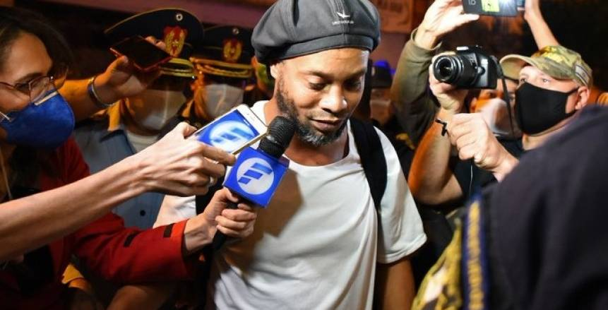 بالكمامات.. استقبال حافل لرونالدينيو بعد خروجه من السجن في باراجواي (فيديو)