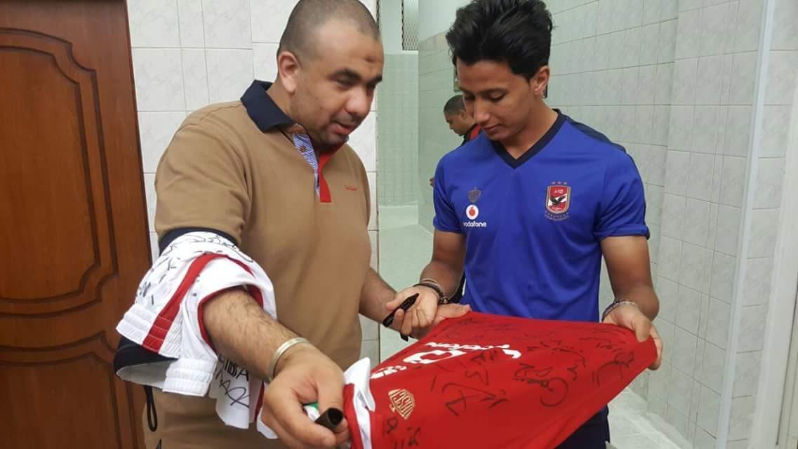 لاعبو الأهلي يوقعون على قميص الفريق لصالح جميعة رعاية اللاعبين القدامى